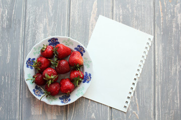 Strawberries in white plate on wooden grey desk.