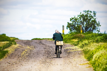 woman riding a bike on a country road, sky background