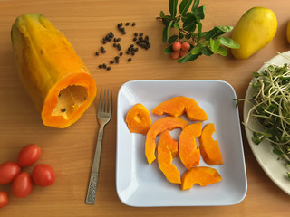 Papaya slices on plate, mango and tomatoesm on table