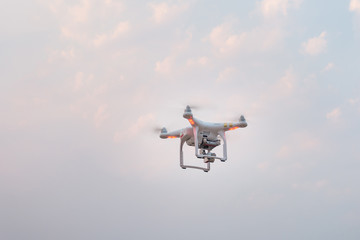 Flying drone with camera on the evening sky
