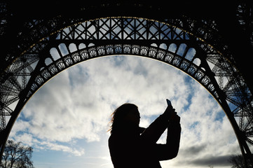 Silhouette of a woman taking pictures with a smartphone under the Eiffel Tower, Paris