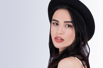 Closeup portrait of a charming woman with brown eyes in black hat