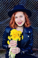 girl in a black jacket and hat with a bouquet of dandelions