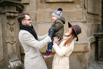 Young hipster couple with baby walking old town streets