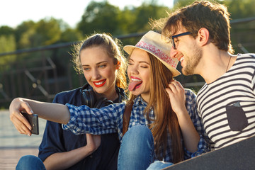 Smiling friends making selfie outdoors