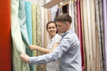 Couple buying colorful curtain samples hanging in store