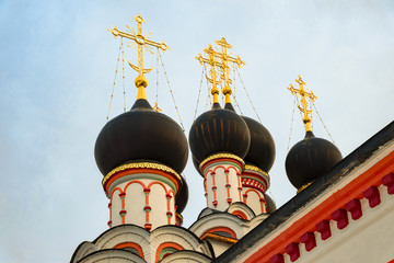 Domes with golden crosses of old Russian Orthodox church in the monastery