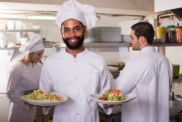 Crew of professional cooks working at restaurant