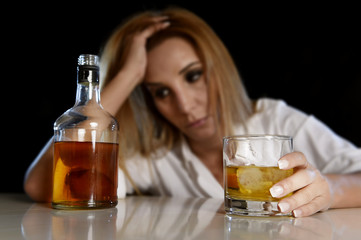 drunk alcoholic woman wasted and depressed holding scotch whiskey glass looking thoughtful to bottle