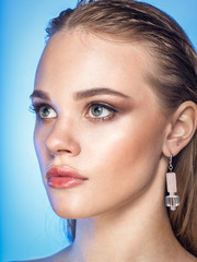 close up studio beauty portrait of young blonde caucasian woman model with wet hair, blue eyes, professional make-up