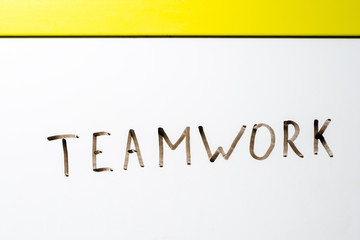 the word teamwork written on a white board marker