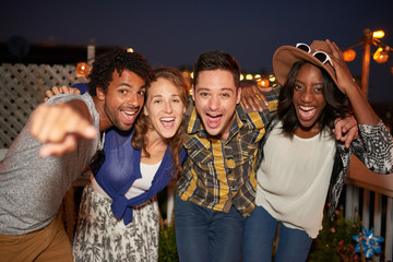 Multi-ethnic millenial group of friends taking a flash selfie photo with mobile phone on rooftop terrasse at night time