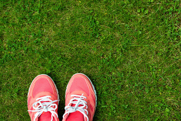 Fitness concept, pink sneakers on green grass, top view