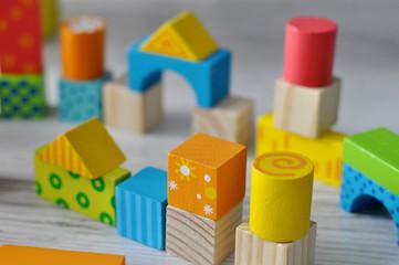 Obraz Kolorowe drewniane klocki ustawione obok siebie i na sobie przypominają budowle tworzące miniaturowe miasteczko - fototapety do salonu