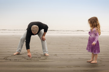 Grandfather drawing heart in sand granddaughter (4-5) watching