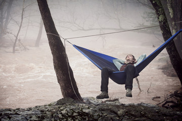 Young male hiker relaxing in hammock next to river
