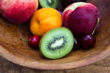 Fresh fruits in wooden bowl