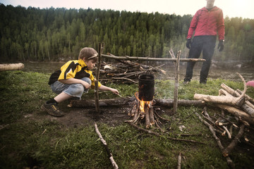 Father and son (8-9) preparing campfire on riverbank