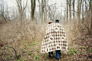 Teenage girl (16-17) walking through woods with her boyfriend