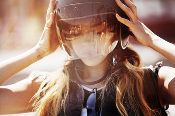 Young woman putting on helmet