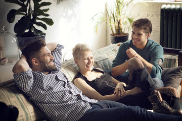 Friends laughing on sofa