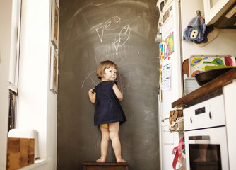 Portrait of girl (2-3) standing by black wall