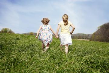 Two girls (4-5, 6-7) running through field