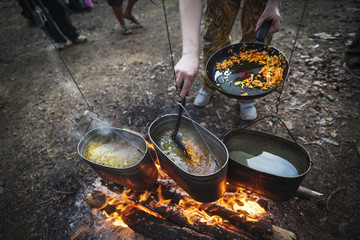 Cooking pans hanging above campfire close-up