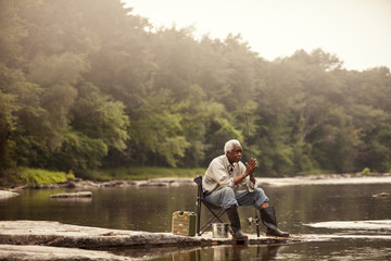 Fisherman sitting on chair near river