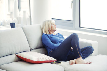 Senior woman sitting in sofa at home