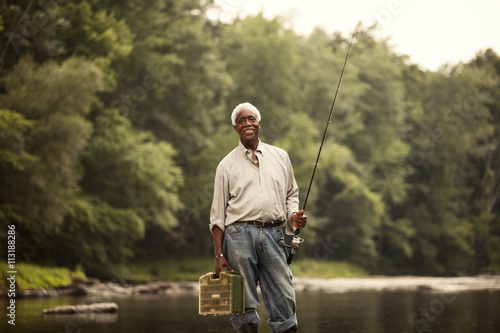 Senior man with fishing rod by river stock photo and for Senior fishing license