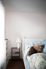 Woman covering face on bed