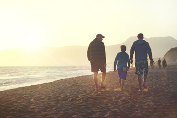 Boy (8-9) with father and grandfather walking on beach