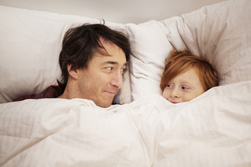 Father and son lying in bed under cover