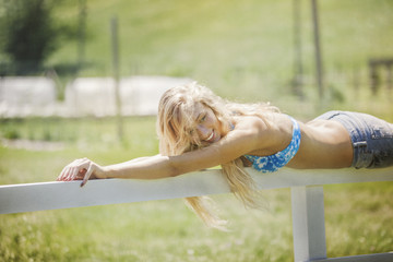 Young woman relaxing on fence