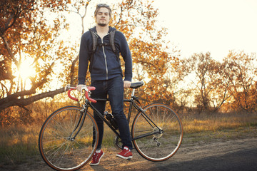 Young man posing with bicycle at sunset