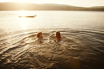 Boy and girl swimming in lake