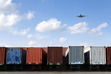 Airplane flying over row of freight containers