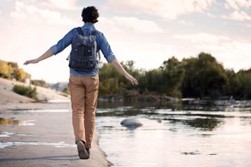 Man walking along concrete bank of river