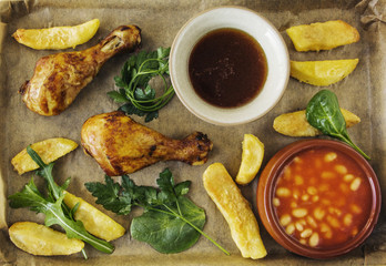 Cooked chicken with french fries herbs and sauce