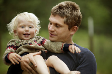 Father holding smiling son (12-17 months)