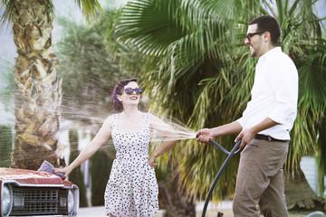 Stylish couple washing car together