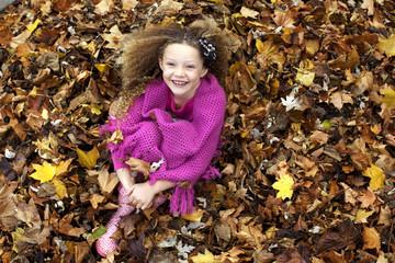 Girl (8-9) sitting in pile of leaves