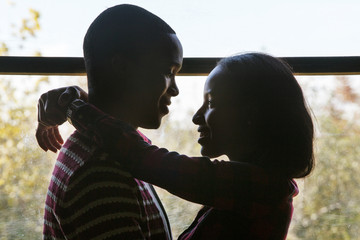 Young couple standing by window and embracing