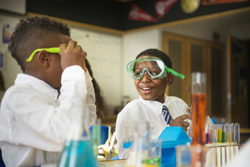 Students wearing safety goggles in science classroom