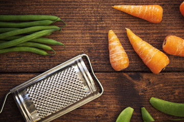 Vegetables and small grater on table