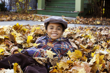 Boy (8-9) Playing In Fall Leaves