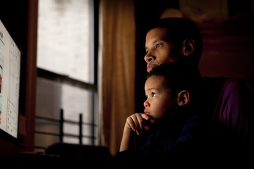 Father and son (4-5) watching computer monitor
