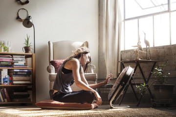 Side view of young woman sitting near fan at home