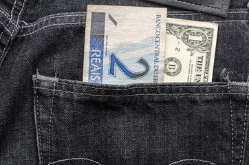 One dollar and two brazilian money inside jeans pocket